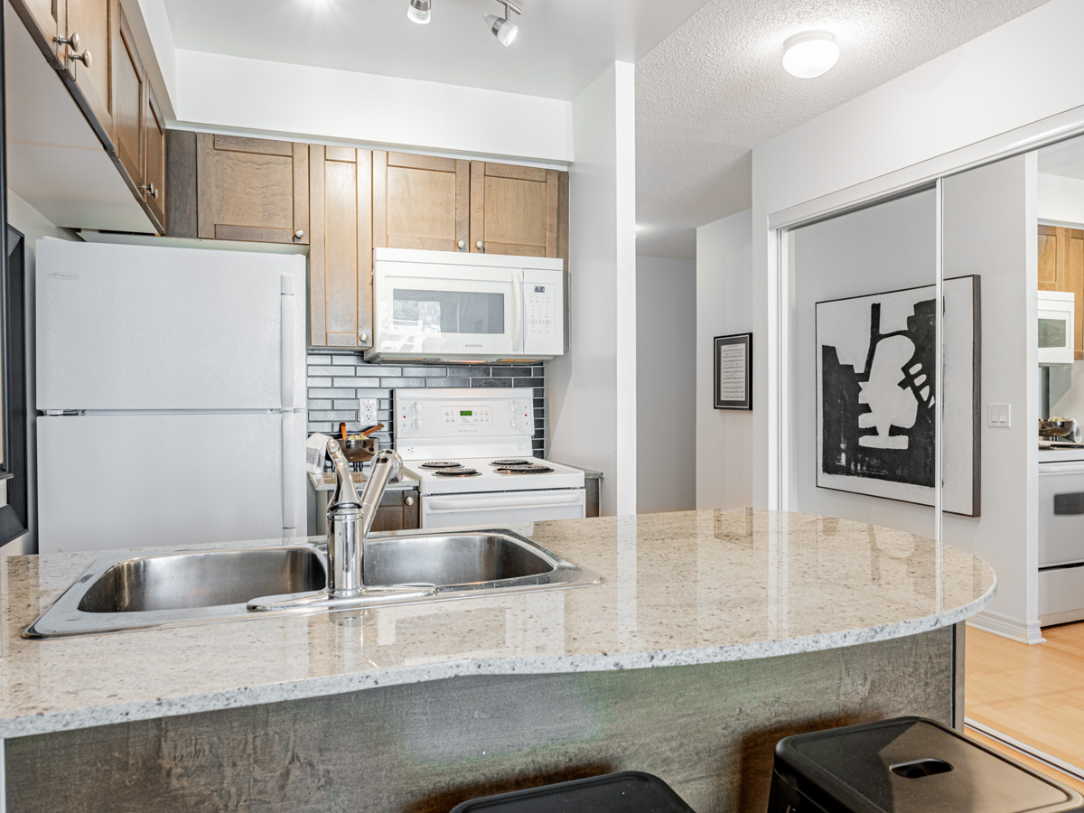 Cabinets, counters, back-splash and appliances shining under kitchen track-lights.