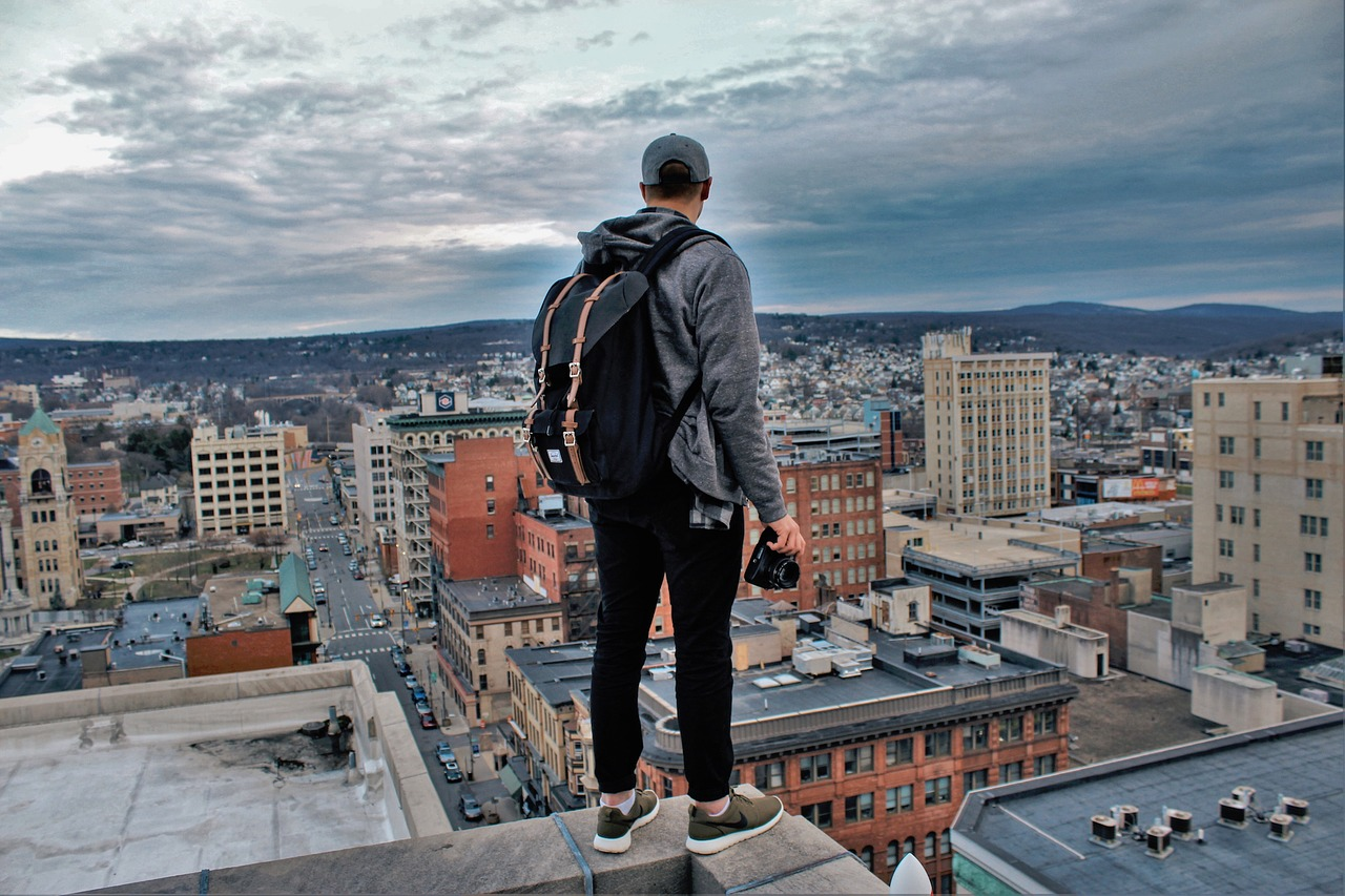 Young man standing on edge of building looking down at city.