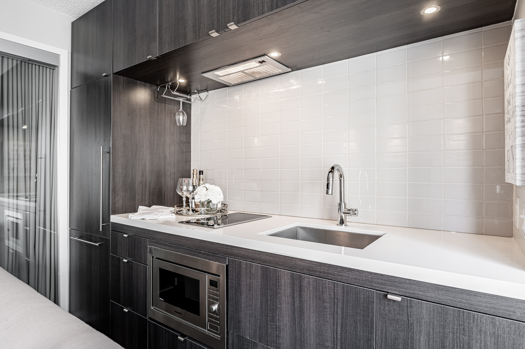 Kitchen with recessed lighting and wine glass rack.