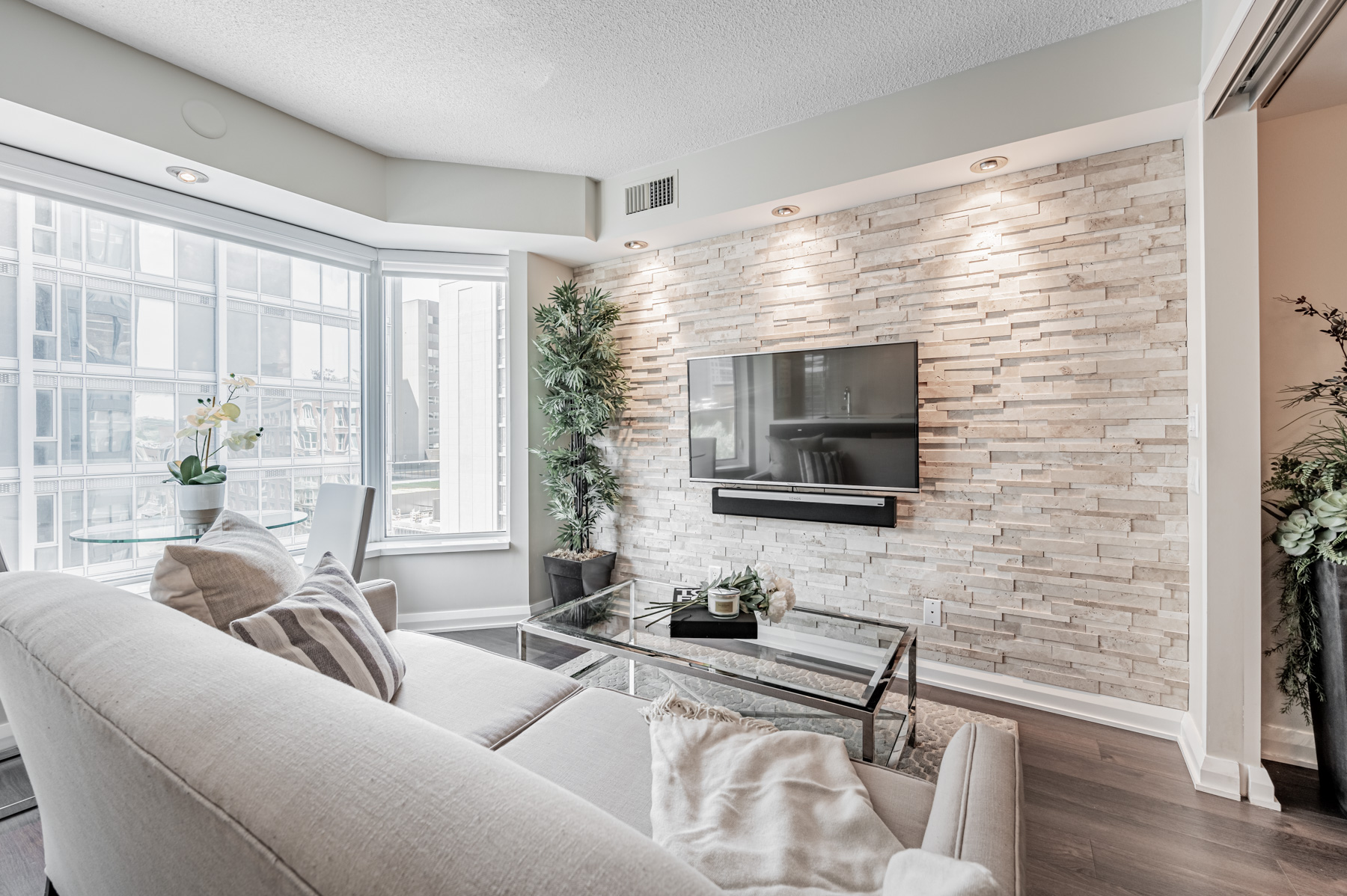 155 Yorkville Ave Unit 712 living room with lightly coloured stone accent wall.