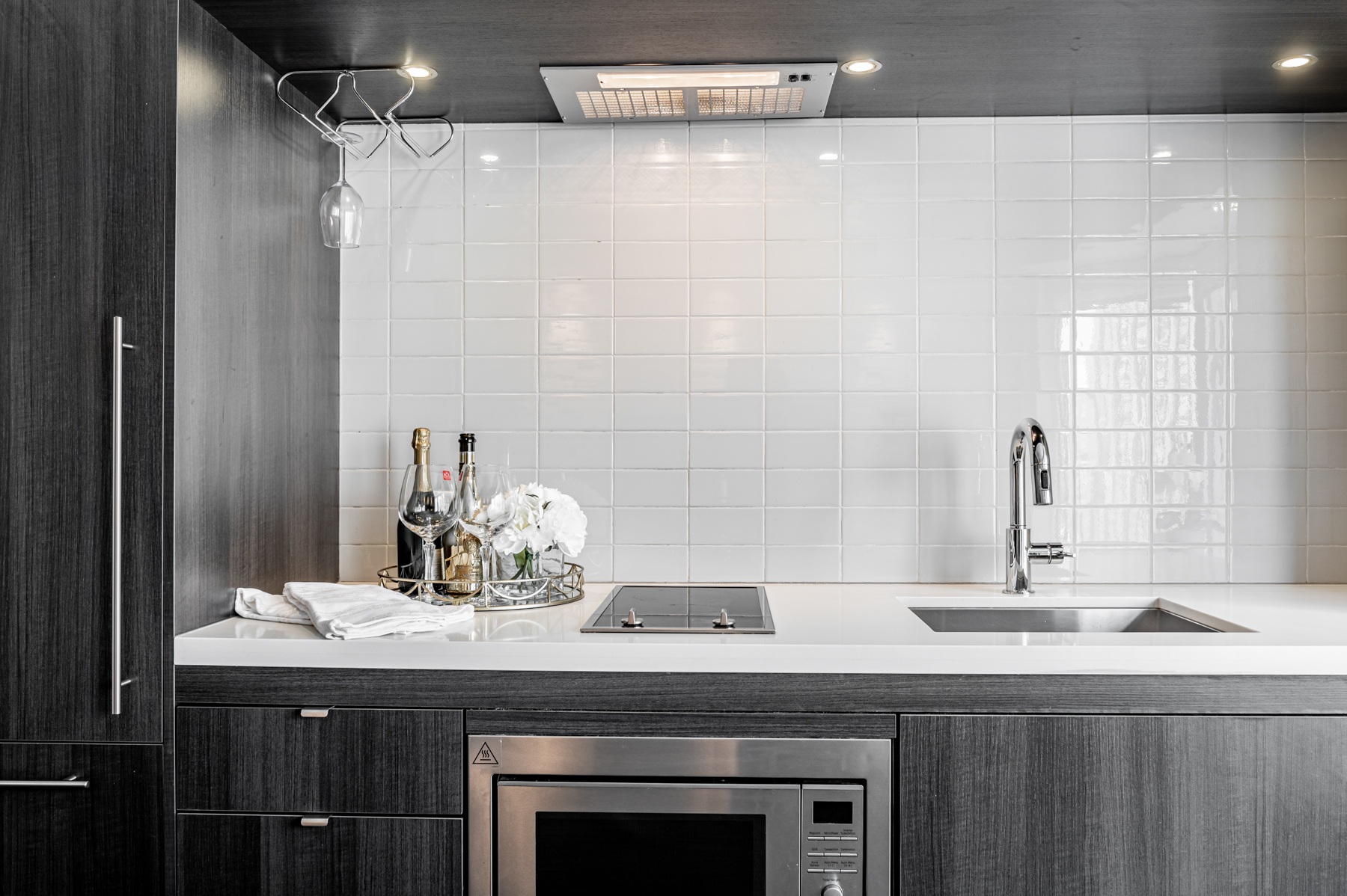 Condo kitchen with dark cabinets, white counters and tiled back-splash.