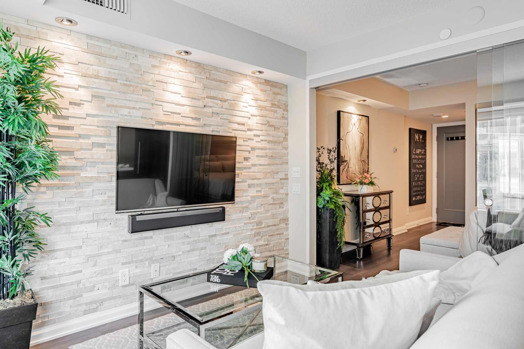 155 Yorkville Ave Unit 712 living room accent wall with mounted TV and Sonos speaker system.