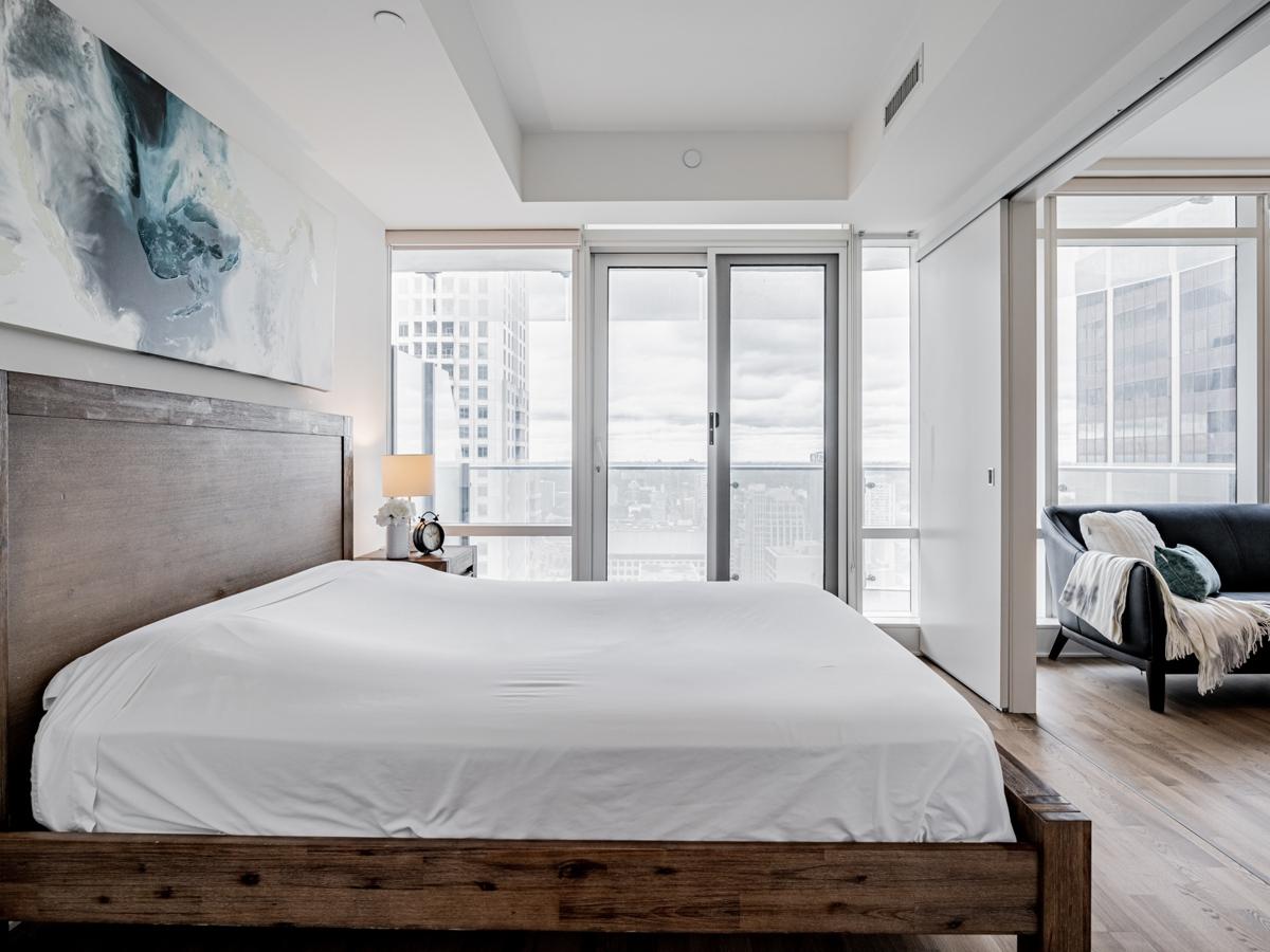 Condo bedroom with walk-out balcony.