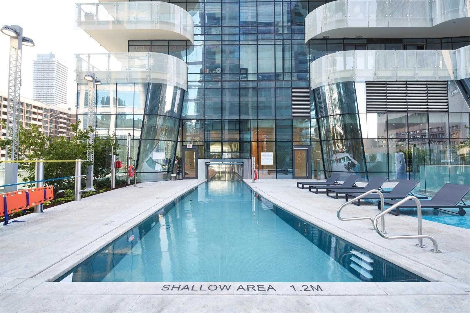 1 Bloor St E condo large swimming pool with lounge seating amenity.